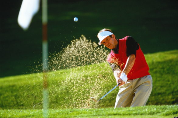 Golfer chipping ball out of bunker creating sand spray, flag in fore